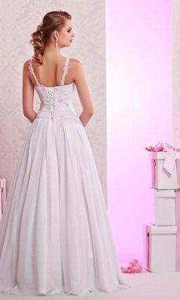 Пышное свадебное платье с кружевной отделкой закрытого лифа и спинкой с тонкими бретелями.