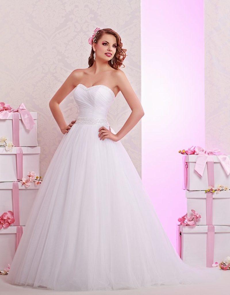 Лаконичное свадебное платье пышного кроя с глянцевым бисерным поясом.