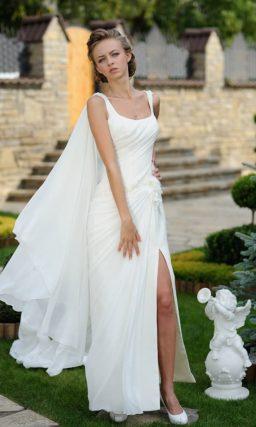 Прямое свадебное платье с разрезом на юбке и роскошной накидкой сзади.