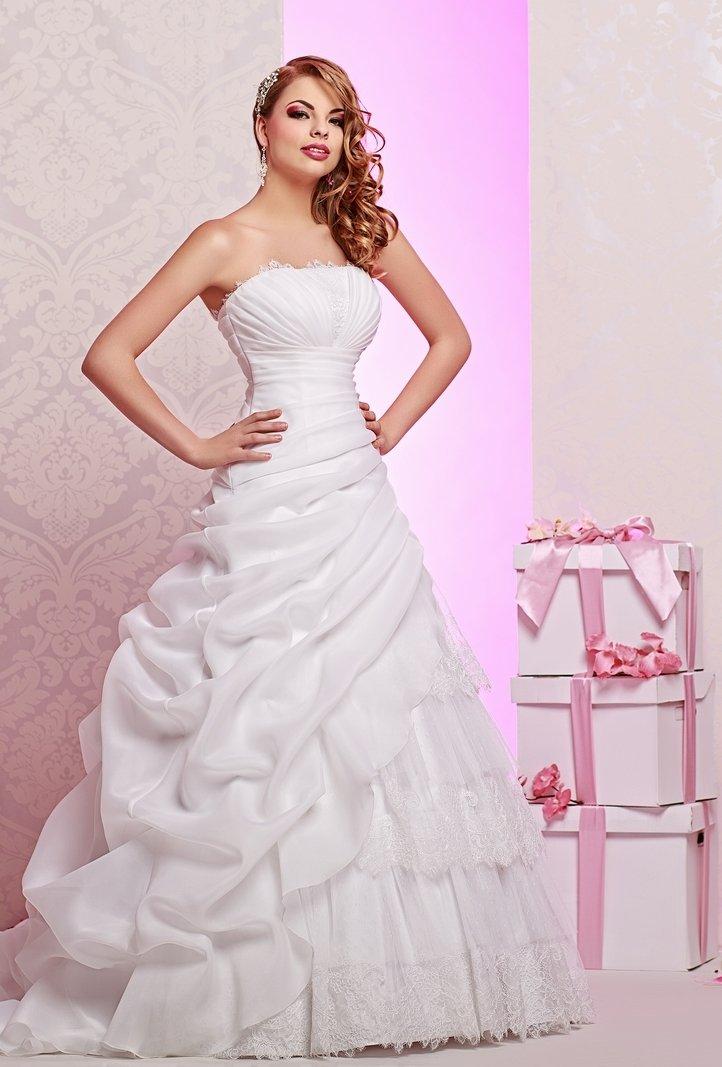 Свадебное платье с кружевным лифом прямого кроя и оборками на пышной юбке.