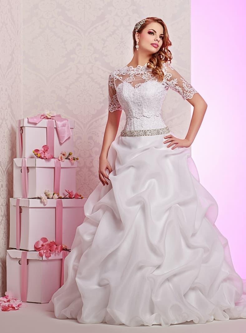 Закрытое свадебное платье с пышной юбкой, покрытой эффектными складками ткани.