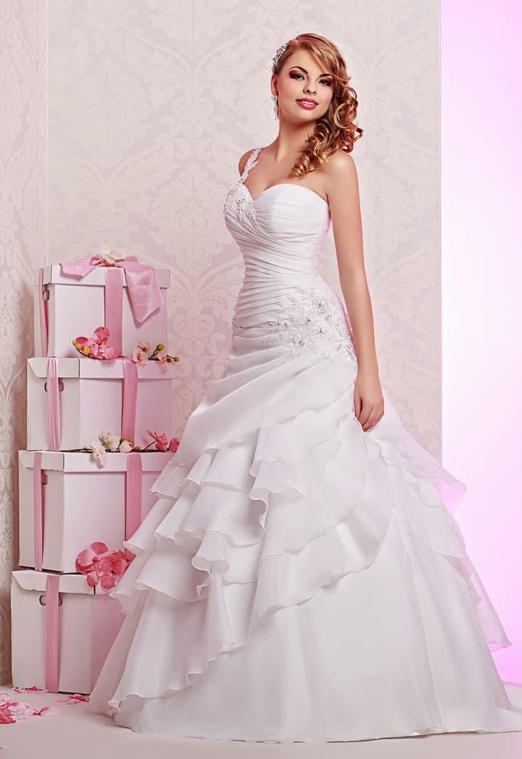 Нежное свадебное платье с отделкой из пышных полупрозрачных драпировок.