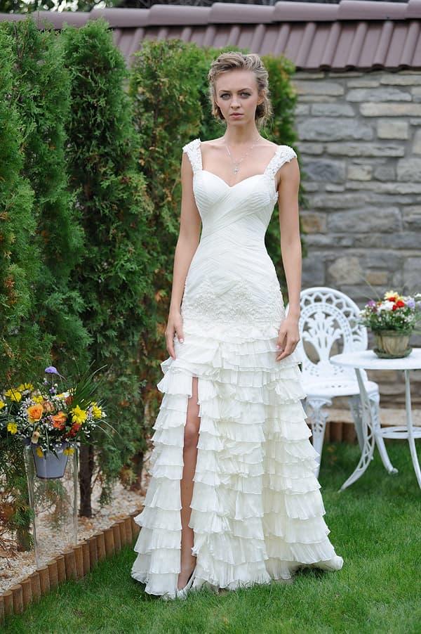 Прямое свадебное платье с оборками и разрезом сбоку на юбке.