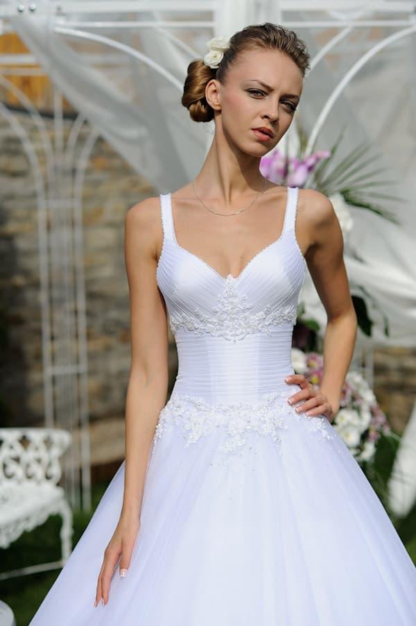 Пышное свадебное платье с глянцевым корсетом с узкими бретелями, украшенным бисером.
