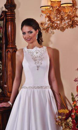 Глянцевое свадебное платье с закрытым верхом, заниженной талией и декором из бисера.
