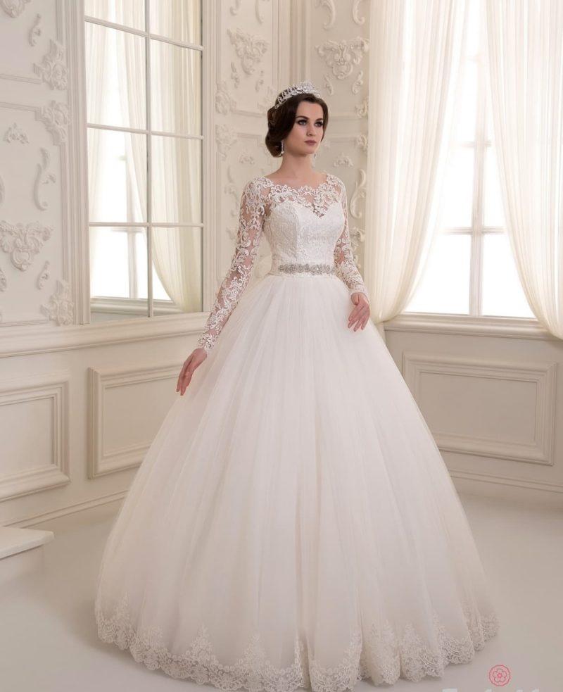 Пышное свадебное платье с кружевным верхом и сияющим поясом на талии.