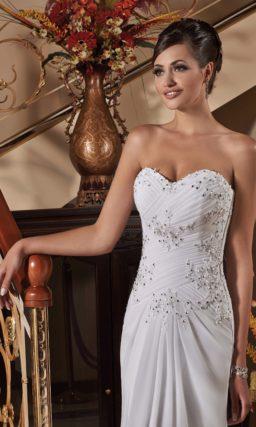 Свадебное платье с корсетом, украшенным драпировками и серебристой вышивкой.