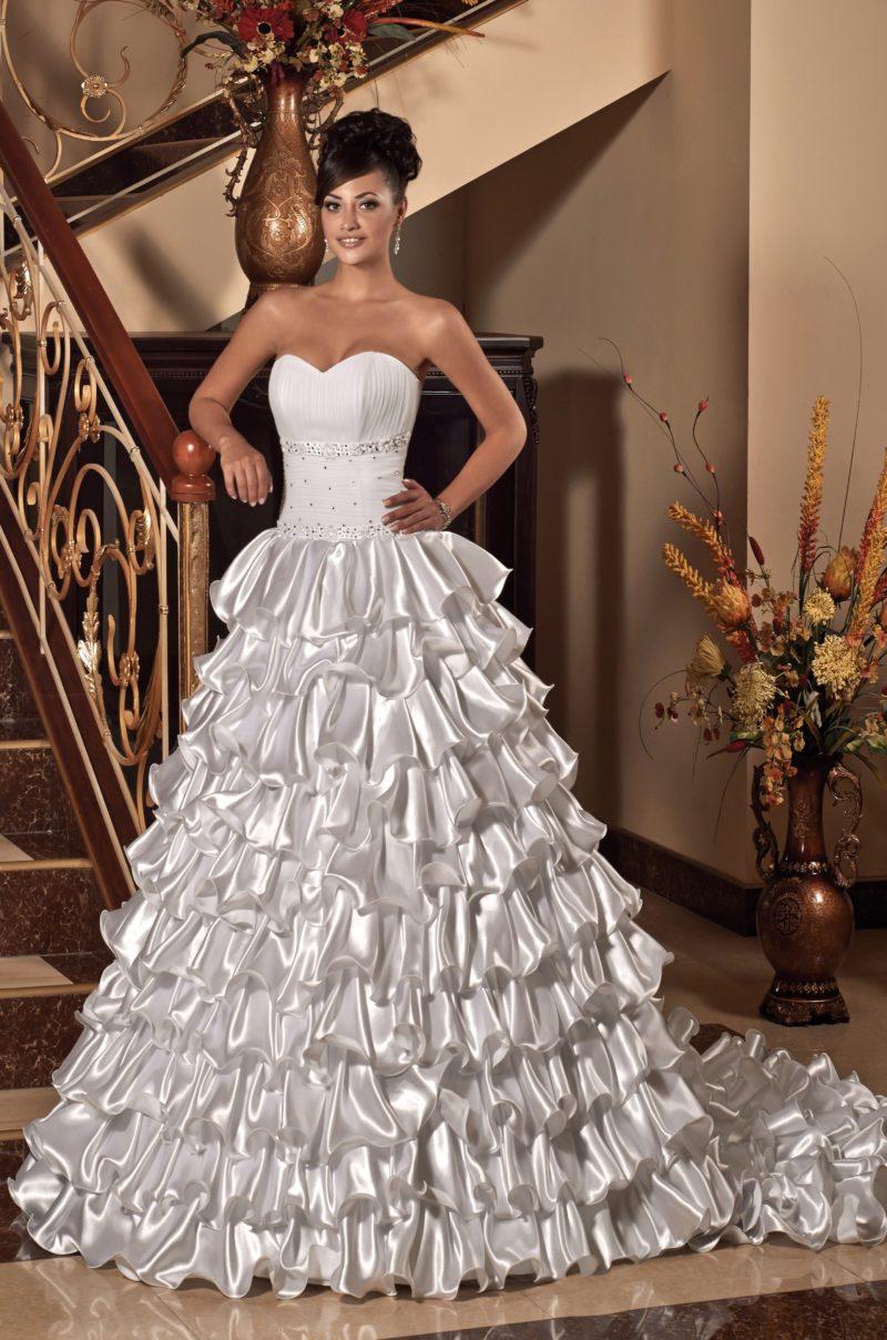 Восхитительное свадебное платье с открытым верхом и пышной юбкой с атласными оборками.