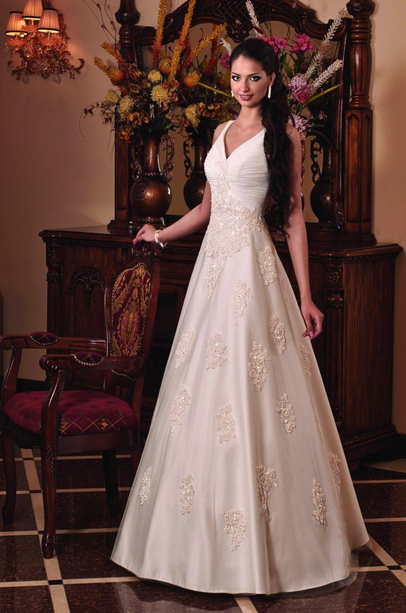Торжественное свадебное платье А-силуэта с декором из кружева и V-образным верхом.