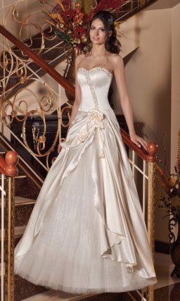 Кремовое свадебное платье из глянцевой ткани, украшенное оборками по юбке.
