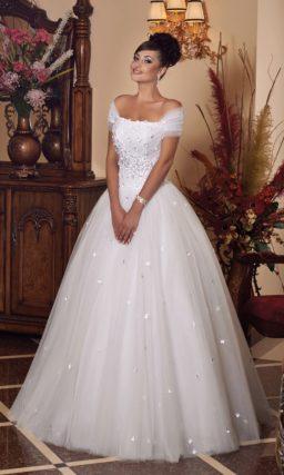 Пышное свадебное платье с романтичным объемным декором и бретелями на предплечьях.