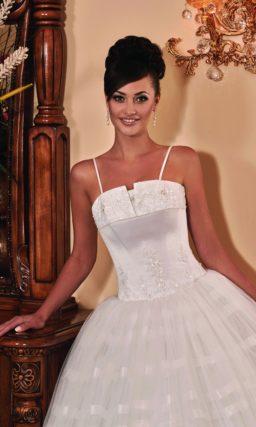 Свадебное платье с оригинальным лифом и многослойной юбкой с горизонтальными полосами.