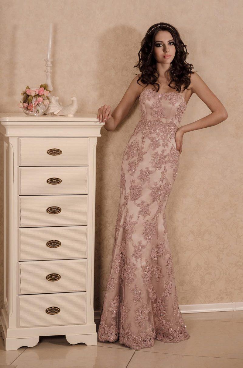 Атласное свадебное платье кремового цвета, покрытое плотным кружевным декором в тон.