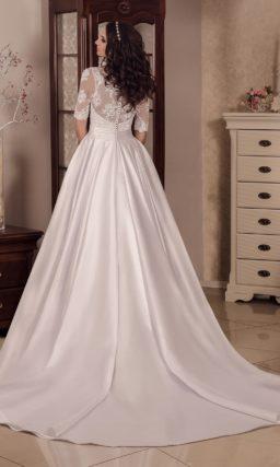Глянцевое свадебное платье с юбкой с длинным шлейфом и фактурным верхом с изящным рукавом.