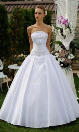 Роскошное свадебное платье с пышной юбкой с вертикальными складками по всей длине.