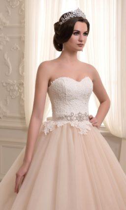 Кремовое свадебное платье с пышной юбкой со шлейфом и белым корсетом.