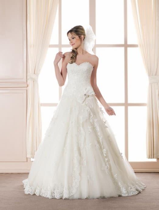 Свадебное платье с кружевной юбкой А-силуэта и бантом на уровне талии.