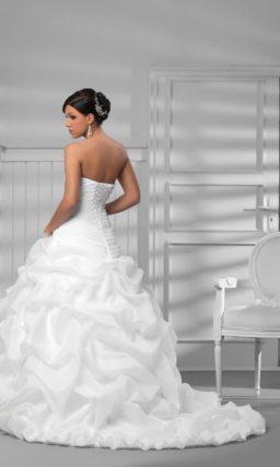 Свадебное платье с пышными оборками на юбке и серебристым декором корсета.