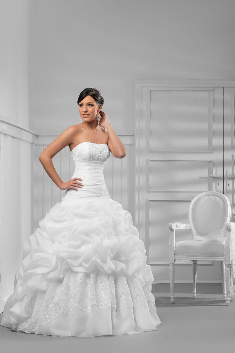 Стильное свадебное платье с лифом прямого кроя и пышной юбкой с длинным шлейфом.