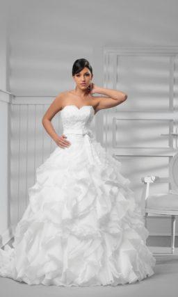 Роскошное свадебное платье с оборками на юбке и длинным шлейфом сзади.