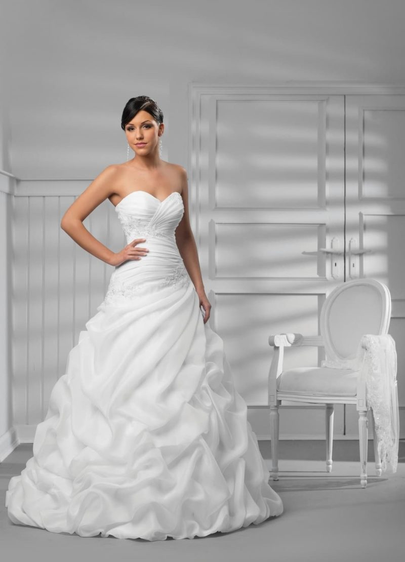 Открытое свадебное платье с женственным лифом и романтичными оборками на юбке.