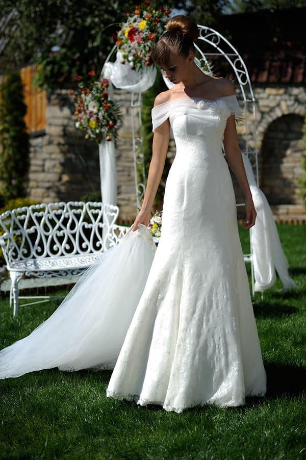 Открытое свадебное платье с широкими бретелями на предплечьях и облегающей юбкой.