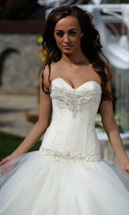 Свадебное платье с фактурным лифом, заниженной талией и многоуровневой юбкой.