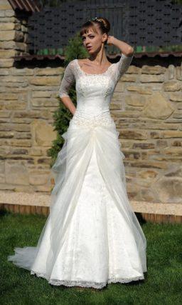 Свадебное платье с круглым декольте и тонкой тканью, задрапированной по юбке.