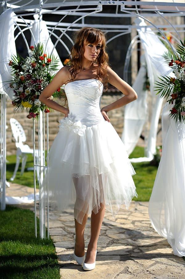 Короткое свадебное платье с атласным верхом и притягательной юбкой с оборками.