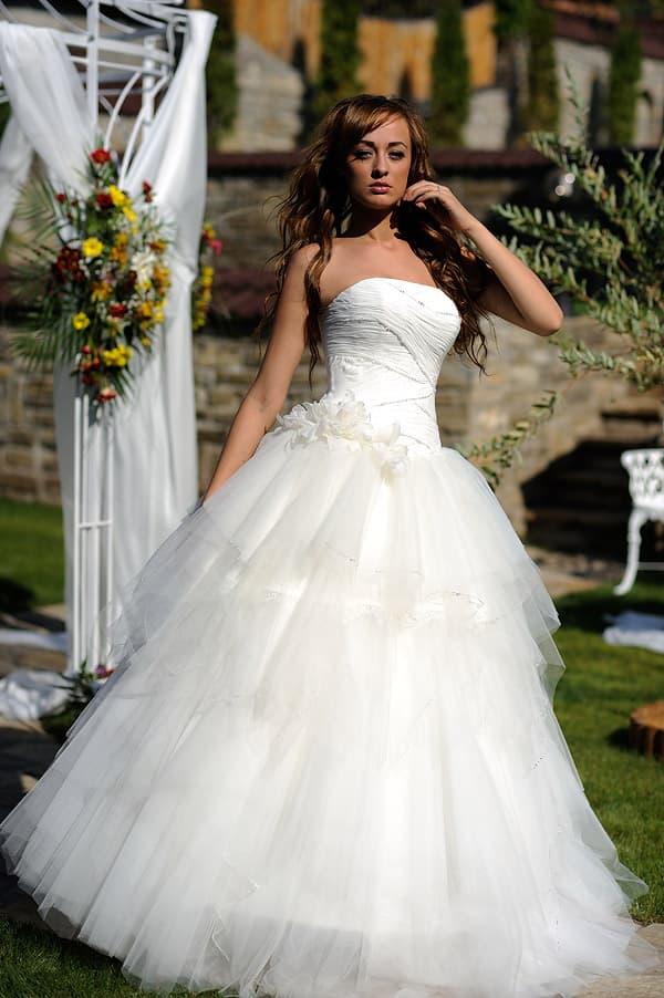 Открытое свадебное платье с романтичными бутонами на талии и воздушным подолом.
