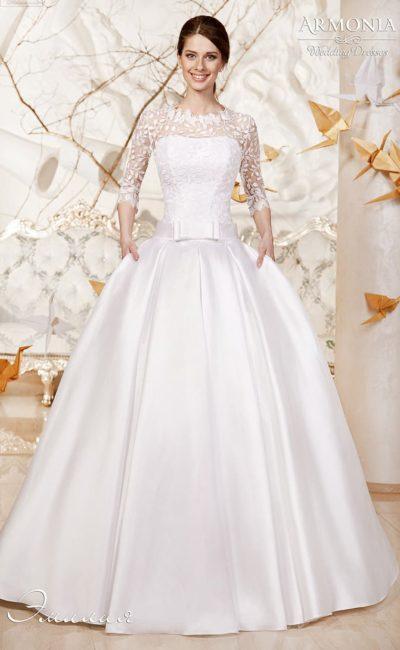 Подчеркнуто пышное свадебное платье с атласной юбкой, украшенное бантом на талии.