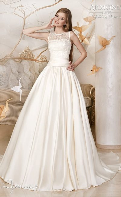 Нежное свадебное платье из атласной ткани с множеством складок на юбке со шлейфом.