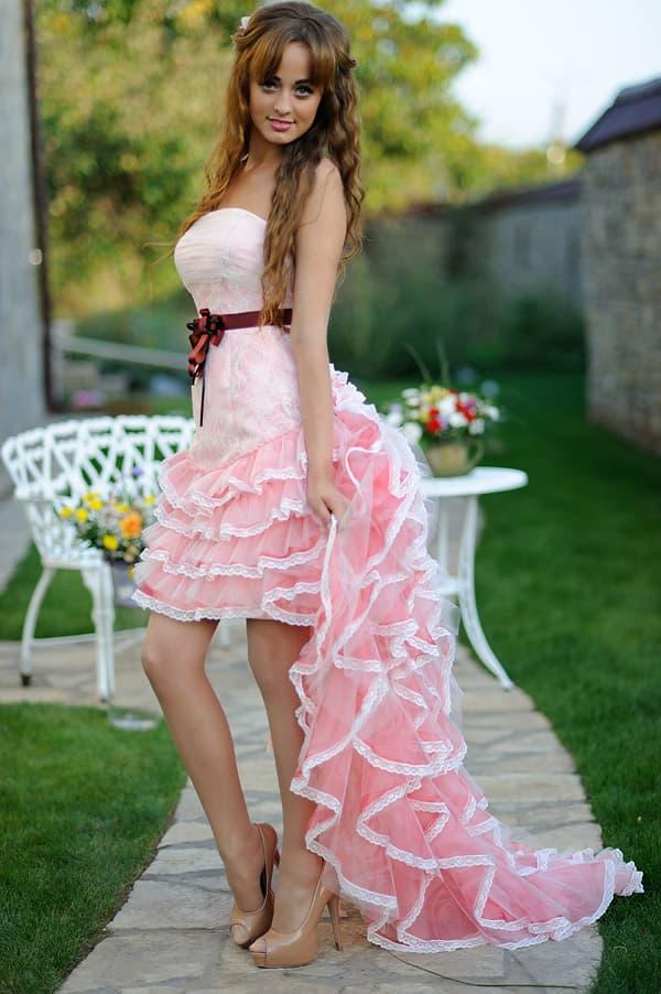 Необычное свадебное платье со шлейфом из розовых оборок и бордовым поясом.