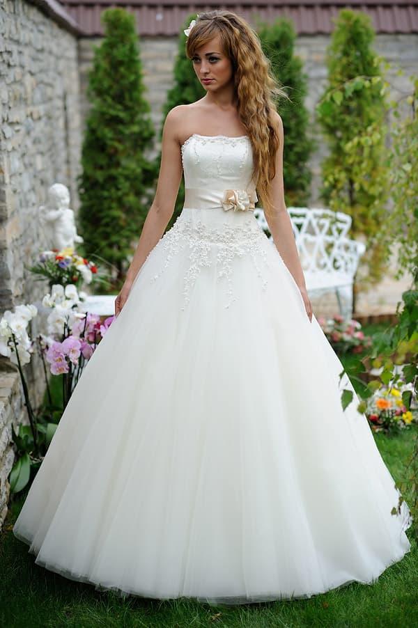 Пышное свадебное платье с фактурным декором и атласным кремовым поясом.