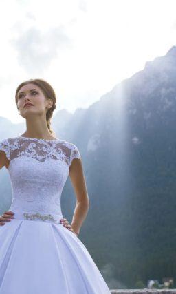 Свадебное платье с округлым декольте, короткими рукавами и вертикальными складками по подолу.