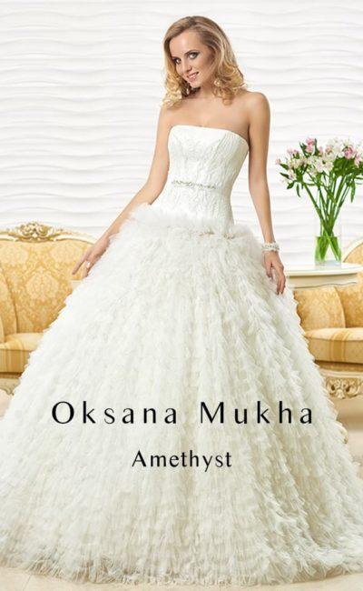 Стильное свадебное платье с лифом прямого кроя и воздушной отделкой пышной юбки.