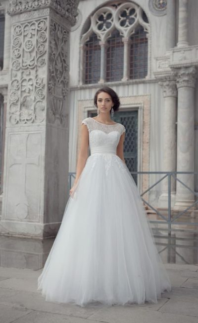 Пышное свадебное платье с закрытым лифом с округлым вырезом и широким поясом с драпировками.