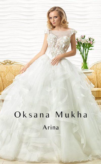 Пышное свадебное платье с полупрозрачными оборками по подолу и объемной отделкой корсета.