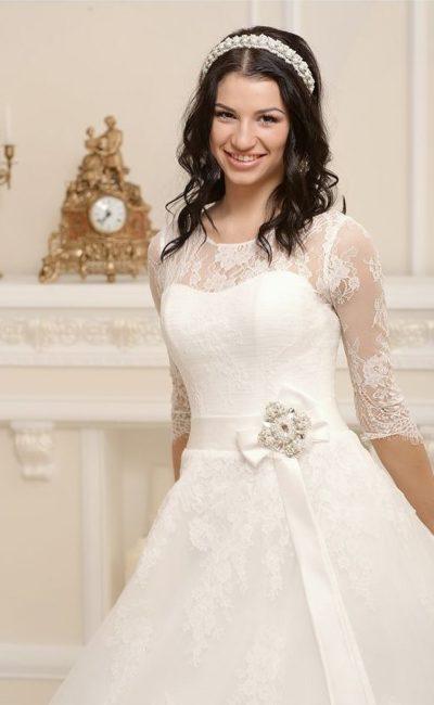 Закрытое свадебное платье с кружевным декором и атласным поясом, сбоку украшенным бантом.