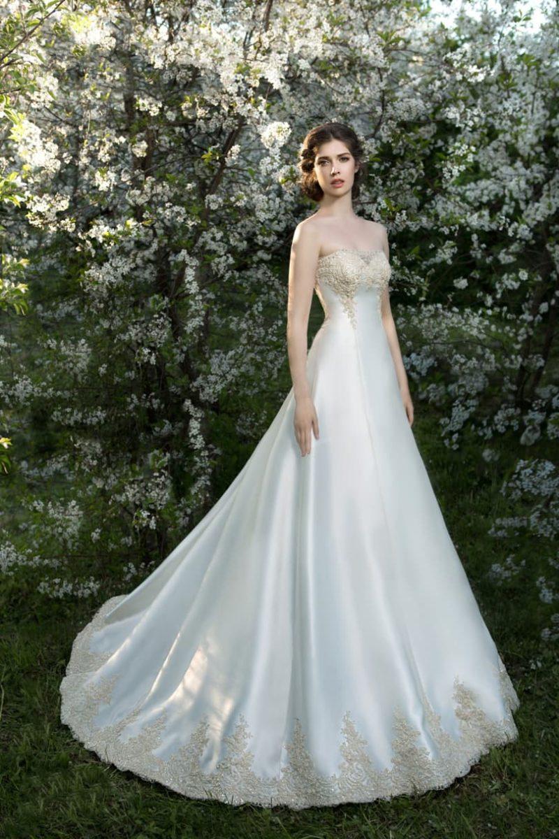 Элегантное свадебное платье с классического кроя лифом и золотистой вышивкой в качестве декора.