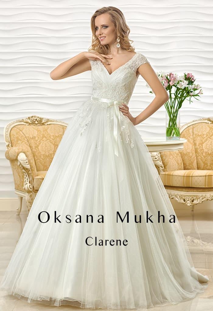 Воздушное свадебное платье с узким атласным поясом и V-образным вырезом.