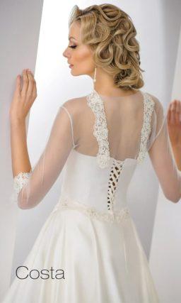 Женственное свадебное платье А-кроя цвета слоновой кости с полупрозрачным рукавом.