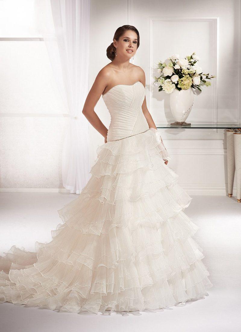 Свадебное платье с роскошным слоем драпировок по корсету и многоярусным подолом.