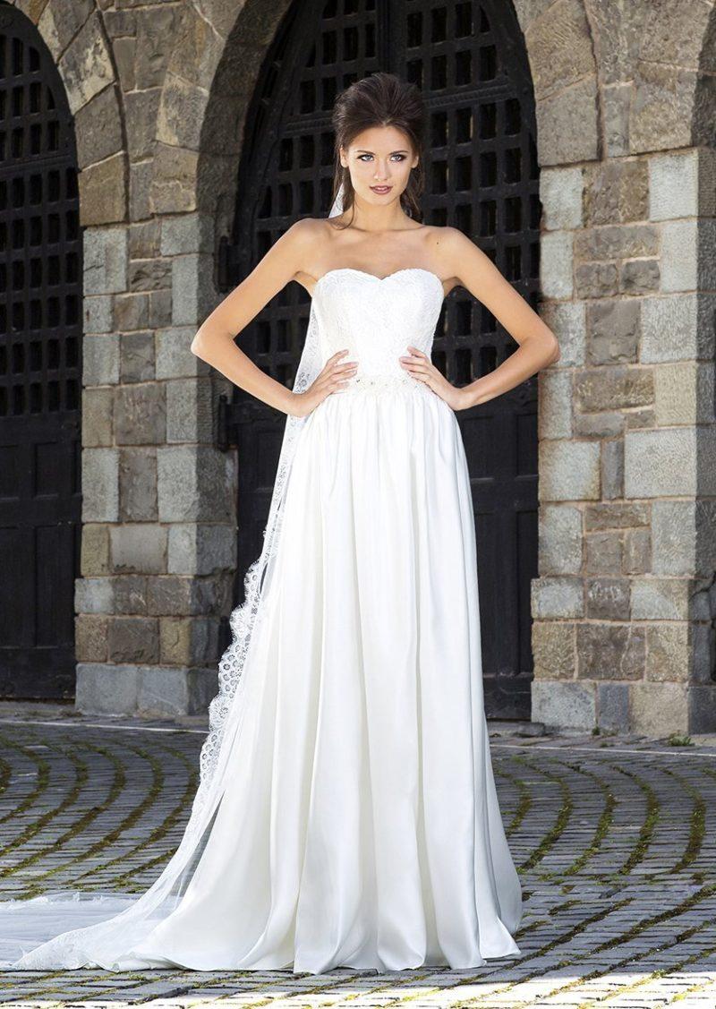 Атласное свадебное платье женственного кроя со складками по подолу и кружевным декором корсета.
