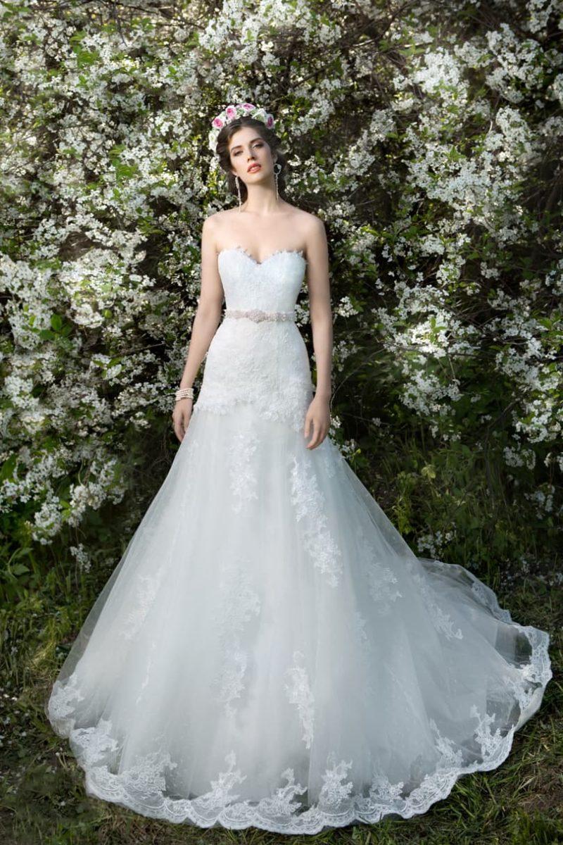 Свадебное платье с фигурным кружевным вырезом и многослойной юбкой с прозрачным верхом.