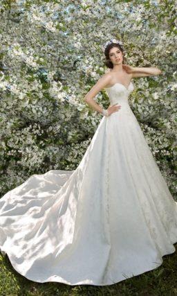 Лаконичное свадебное платье с лифом сердечком и пышной юбкой с длинным шлейфом.