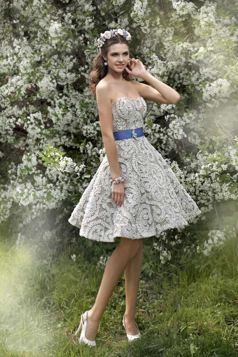 Бежевое свадебное платье пышного кроя с юбкой до колена и синим атласным поясом.