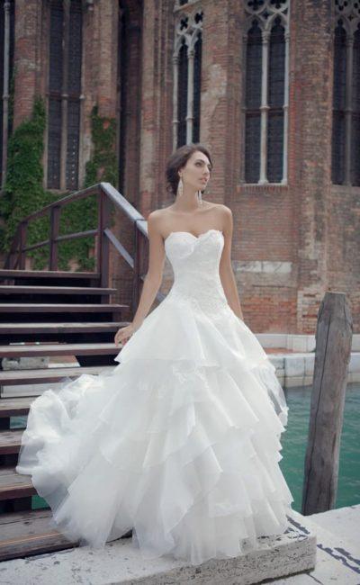 Великолепное свадебное платье с классическим открытым корсетом и волнами тонкой ткани по юбке.