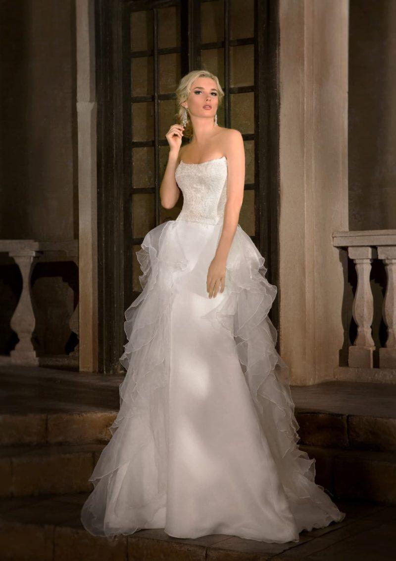 Кокетливое свадебное платье с лаконичной юбкой, дополненной сзади многоярусным пышным шлейфом.