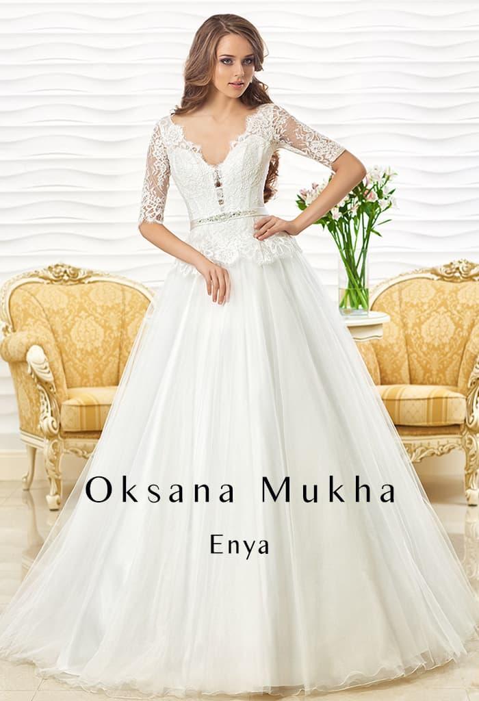 Изящное свадебное платье с кружевным рукавом до локтя и объемной юбкой.